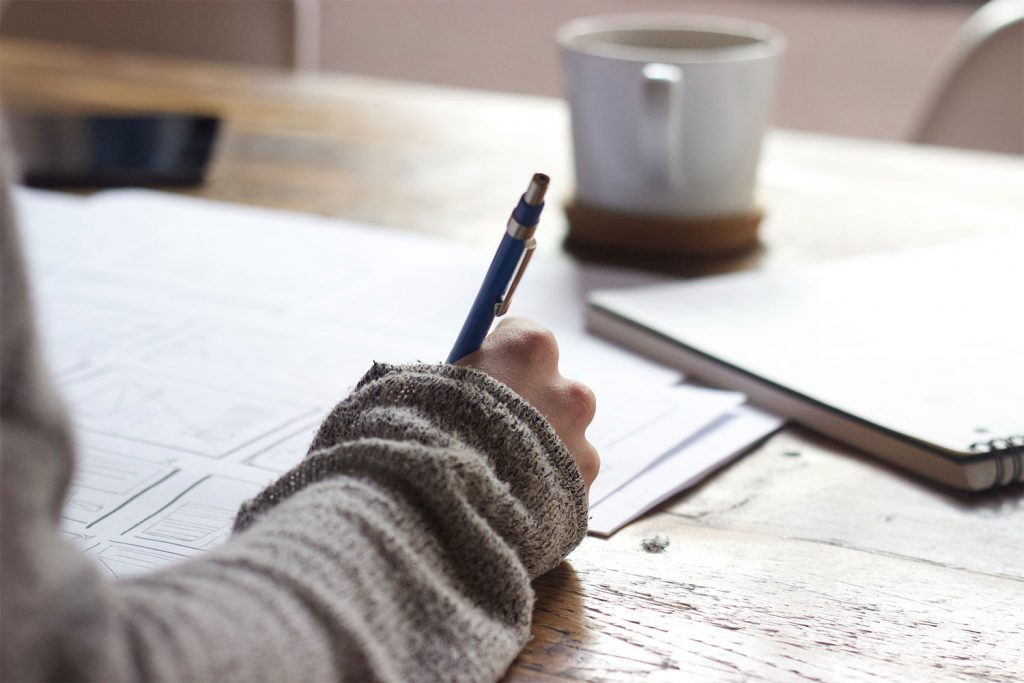 A woman in a beige sweater writing on a piece of paper with a pencil