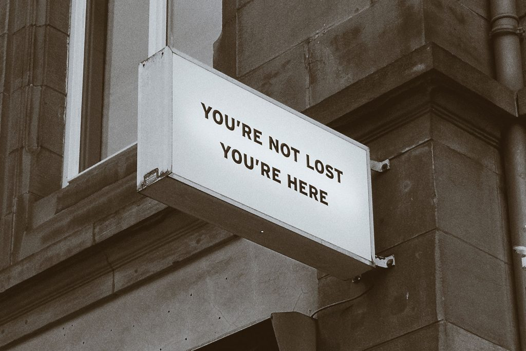 A white sign saying you are not lost, you are here on a brick building