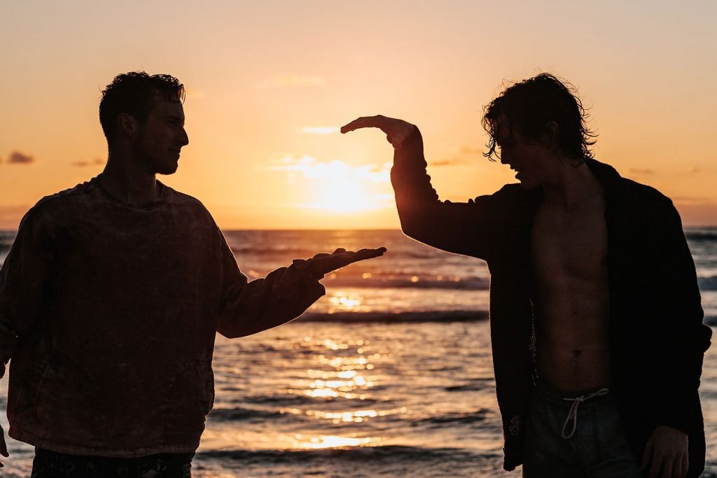 Two men on a beach giving each other high fives with a sunset behind it